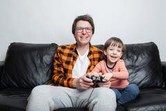 De een weinig knappe jongen en zijn papa zitten op de laag thuis en het spelen videospelletjes met de bedieningshendel De papa en stock foto's
