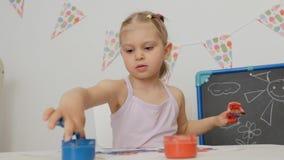 De een weinig leuke meisjeszitting bij de lijst trekt op papier met heldere vingerverven, die haar vingers in kruiken van verf on stock videobeelden