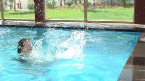 De een weinig vrolijke jongenssprongen in de pool, zijn moeder vangt hem Langzame Motie stock footage
