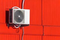 De eenheid van de airconditioning op een rode muur stock afbeelding
