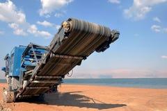 De eenheid van de steengroevemaaimachine met zwaar materiaal Bouwnijverheid het aanleggen van een weg en een hotel op het Dode Ov stock foto