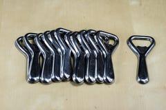 De eenvoudige opener van de metaalplaat op countertop in het restaurant Een zilveren en glanzende flesopener Stock Foto