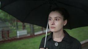 De eenzame droevige vrouw loopt onderaan de straat in zware regen Langzame Motie stock videobeelden