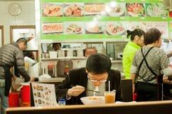 De eenzame jonge mens eet voedsel met honger binnen klein en eenvoudig Chinees restaurant stock fotografie