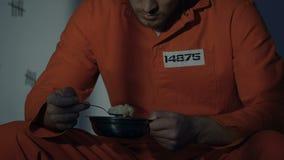 De eenzame Kaukasische gevangene die doende walgen maaltijd weigeren, heeft normaal voedsel, close-up nodig stock video
