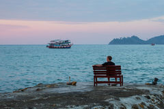 De eenzame mens zit op een bank op de kust bekijkend het overzees Reis Stock Foto's