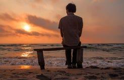 De eenzame mens zit op een bank op de kust genietend van zonsondergang Royalty-vrije Stock Foto's