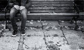 De eenzame mens zit op een houten bank Stock Afbeeldingen