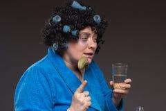 De eenzame rijpe vette alcoholische vrouw drinkt wodka van glazen en Stock Foto's