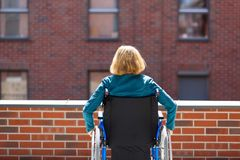 De eenzame vrouw op langs omringde rolstoel bricked gebouwen Royalty-vrije Stock Fotografie