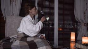 De eenzame vrouw in witte badjas drinkt alcohol in modern hotel in de avond stock video