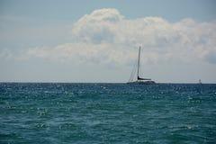 De eenzame zeilboot in het overzees op de horizon, glanst en uitstraling van water Stock Afbeeldingen