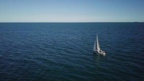 De eenzame zeilboot ploegt expance van de oceaan, luchtspruit Jacht van hommel stock videobeelden