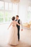 De eerste Dans van het Huwelijk de dansen van het huwelijkspaar op de studio De dag van het huwelijk Gelukkige jonge bruid en bru royalty-vrije stock foto