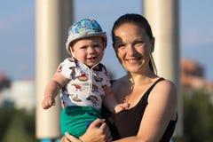 De eerste jongen van de Stappenbaby met moeder in het park Rond heel wat groene gras en bomen in de zomer royalty-vrije stock foto