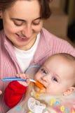 De eerste keer die van de baby alleen eet Stock Fotografie