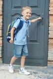 De eerste-nivelleermachine met een rugzak is bij de deur van de school De eerste vraag eind van het schooljaar honger voor kennis stock fotografie