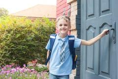 De eerste-nivelleermachine met een rugzak is bij de deur van de school De eerste vraag eind van het schooljaar honger voor kennis stock foto