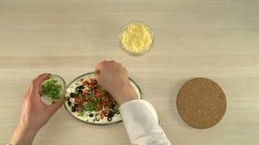De eerste-persoonsmening over chef-kok zet tomaten in salade stock video