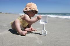 De eerste reis van de baby aan het strand Stock Afbeelding