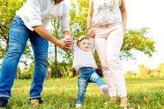 De eerste stappen van de baby De ouders onderwijzen hun kind aan stock foto