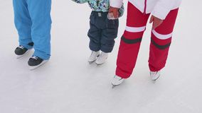 De eerste stappen van een jong kind op vleten Het mamma en de papa onderwijzen een kind om te schaatsen en zijn handen op het ijs stock videobeelden