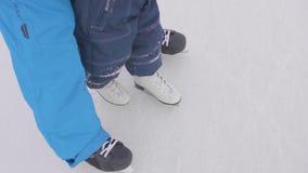 De eerste stappen van een jong kind op vleten De papa onderwijst het kind om te schaatsen en houdt zijn handen Familie en openluc stock videobeelden