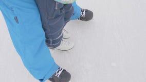 De eerste stappen van een jong kind op vleten De papa onderwijst het kind om te schaatsen en houdt zijn handen Familie en openluc stock footage
