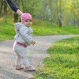De eerste stappen van het jonge geitje De gangen van weinig babymeisje in park stock foto's
