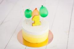 De eerste verjaardag breekt de cake De cake met nummer één en kleine impulsen De groeten van de verjaardag Geel stipkoekje Stock Foto