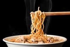 De eetstokjes nemen smakelijke noedels met rook op donkere achtergrond op Ramen in witte kom royalty-vrije stock afbeeldingen