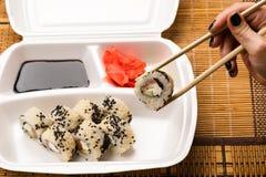 De eetstokjes van de vrouwenholding voor sushibroodje royalty-vrije stock foto