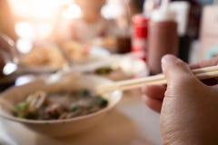 De eetstokjes van de handholding voor het eten van noedels stock foto