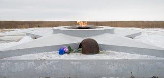 De eeuwige vlam, in geheugen van de slachtoffers van 1941-1945, een kogel doordrong de helm Stock Afbeelding