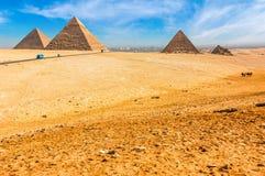 De egyptiska pyramiderna av Giza på bakgrunden av Kairo Miracl Royaltyfri Bild