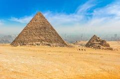 De egyptiska pyramiderna av Giza på bakgrunden av Kairo Miracl Royaltyfria Bilder