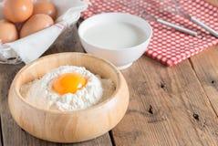 De eierdooier in de bloem met melk en ranselt voor afstraffing op houten lusje stock afbeeldingen