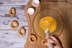 De eierdooier en het wit in glaskom en draad zwaaien over donkere doorstane houten lijst Stock Afbeeldingen