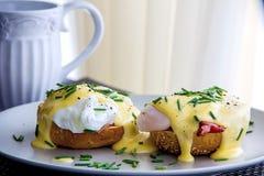 De eieren Benedict roosterden muffins, ham, stroopten eieren, en heerlijke boterachtig hollandaise saus Stock Afbeelding