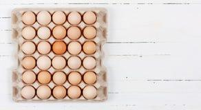 De eieren in de kartonvakjes die op witte houten achtergrond met exemplaarruimte leggen royalty-vrije stock foto