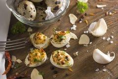 De eieren van Deviledkwartels schikten keurig op houten lijst met decoratie Stock Afbeeldingen
