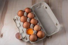 De eieren van de verpakkingskip met ??n op een houten achtergrond worden gebroken die royalty-vrije stock afbeelding