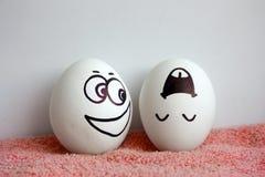 De eieren zijn vrolijk met een te bewonderen gezichtsconcept Stock Foto's