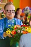 De Eigenaar die van de bloemwinkel met Regeling glimlachen Stock Foto's