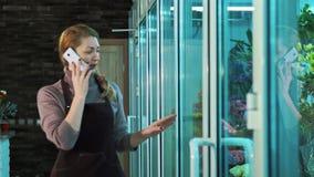 De eigenaar van de bloemwinkel die op de telefoon en de gangen spreken die showcase van bloemen kijken stock video