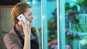 De eigenaar van de bloemwinkel die op de telefoon en de gangen spreken die showcase van bloemen kijken stock footage