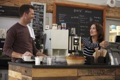 De eigenaars die achter de teller van koffie werken bekijken elkaar stock foto