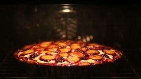 De eigengemaakte bessenpastei met pruimen en braambes wordt gebakken in de oven stock footage