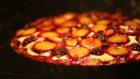 De eigengemaakte bessenpastei met pruimen en braambes wordt gebakken in de oven stock videobeelden