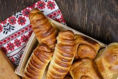 De eigengemaakte broodjes en de gebakjes van verschillende vormen met diverse vullingen worden opgemaakt op vierkante houten plaa stock fotografie